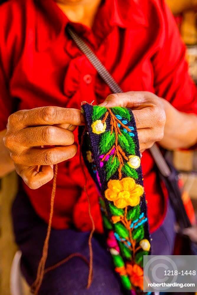 Woman embroidering traditional Alpaca wool hat band, Ayacucho, Peru, South America