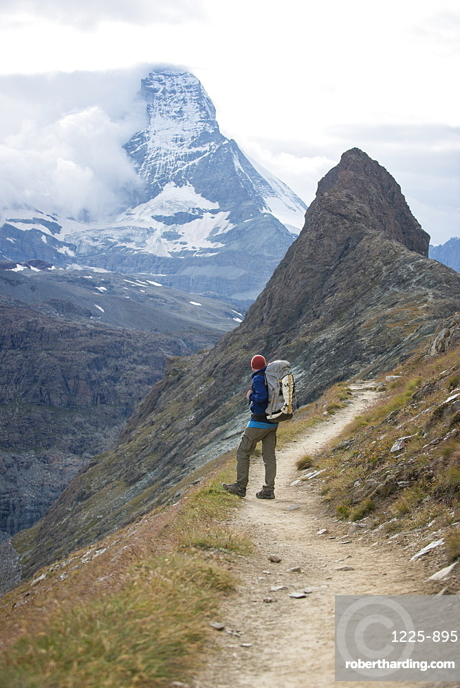 Hiking a trail in the Swiss Alps near Zermatt with a view of The Matterhorn in the distance, Zermatt, Valais, Switzerland, Europe