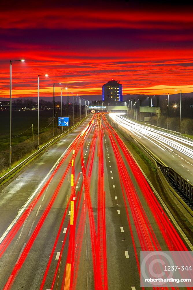 Red sky sunset, traffic light trails, M8 Motorway, Scotland, United Kingdom, Europe