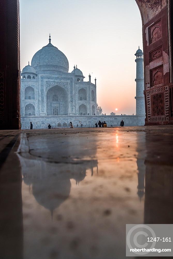 Reflections as the sun rises behind the Taj Mahal, UNESCO World Heritage Site, Agra, Uttar Pradesh, India, Asia