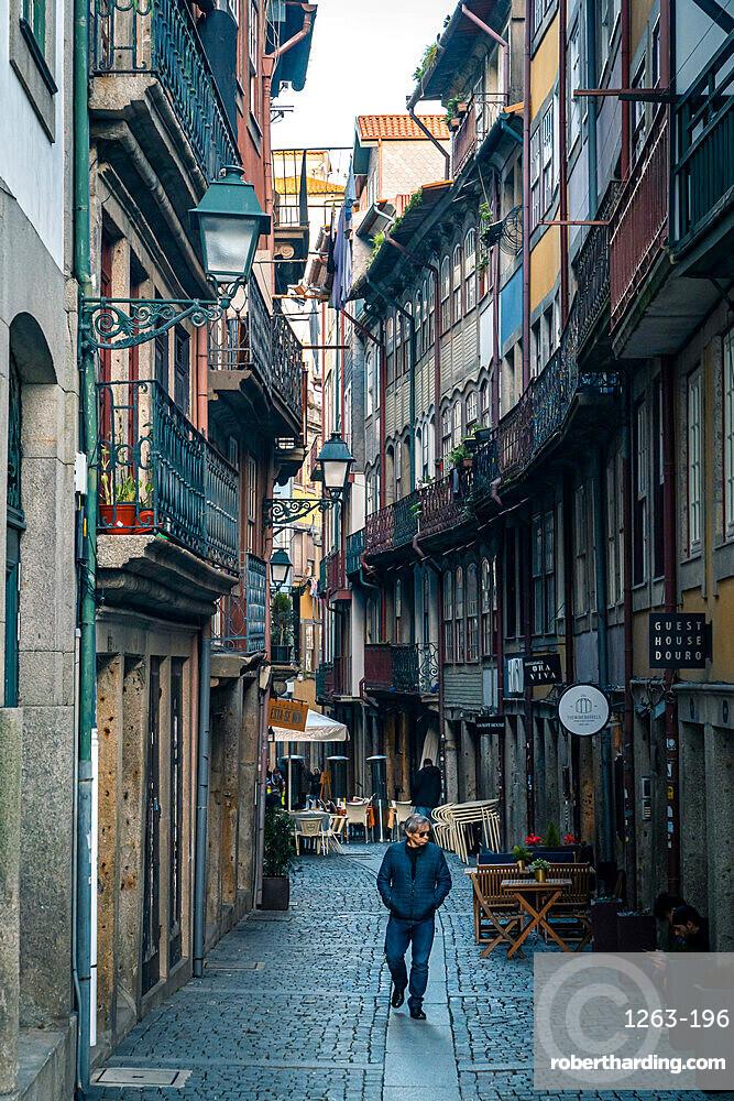 A lone man walking along a back street in Porto, Portugal, Europe