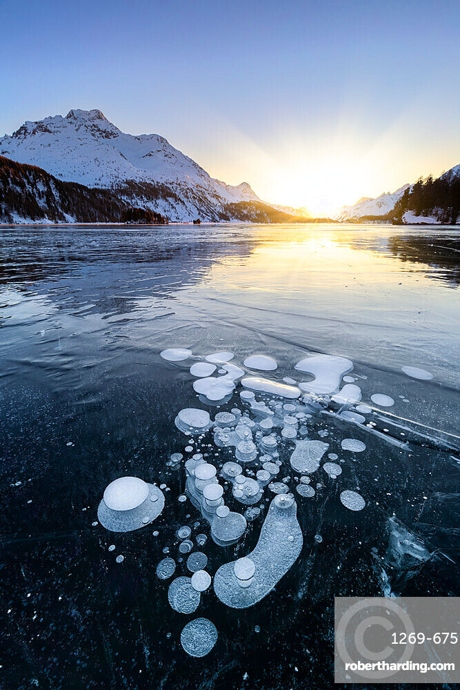 Methane bubbles in the icy surface of Silsersee with snowy peak illuminated by sunset light, Lake Sils, Engadine Valley, canton of Graubunden, Switzerland, Europe