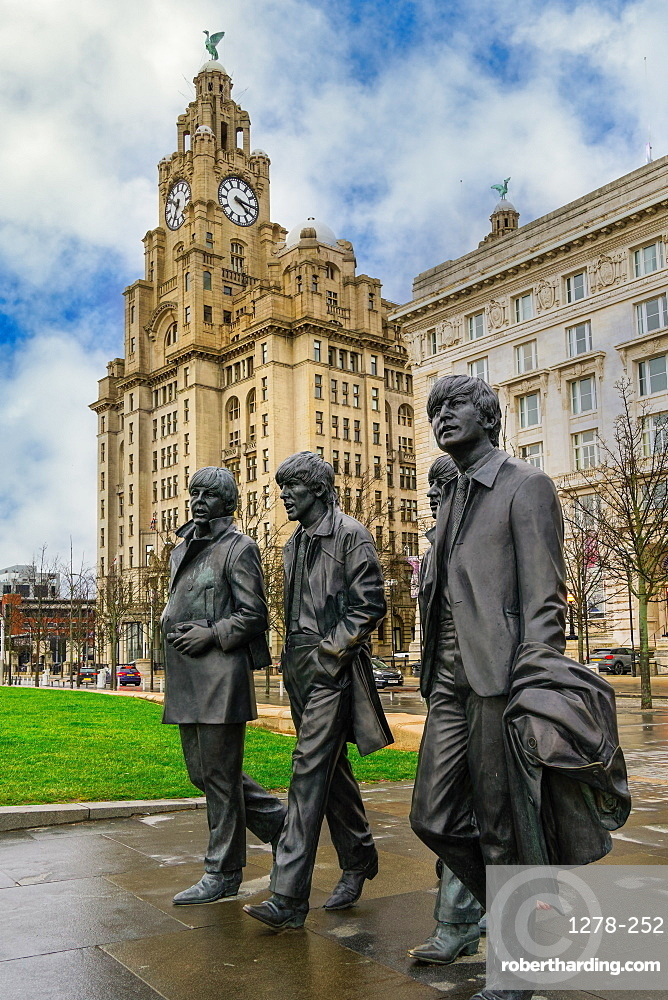 Liverpool, UK The Beatles statue. Bronze art depicting the famous band facing river Mersey with Royal Liver Building background.