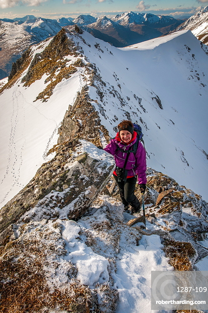 A mature female hill walker on the Brothers Ridge above Glen Shiel, Kintail in winter