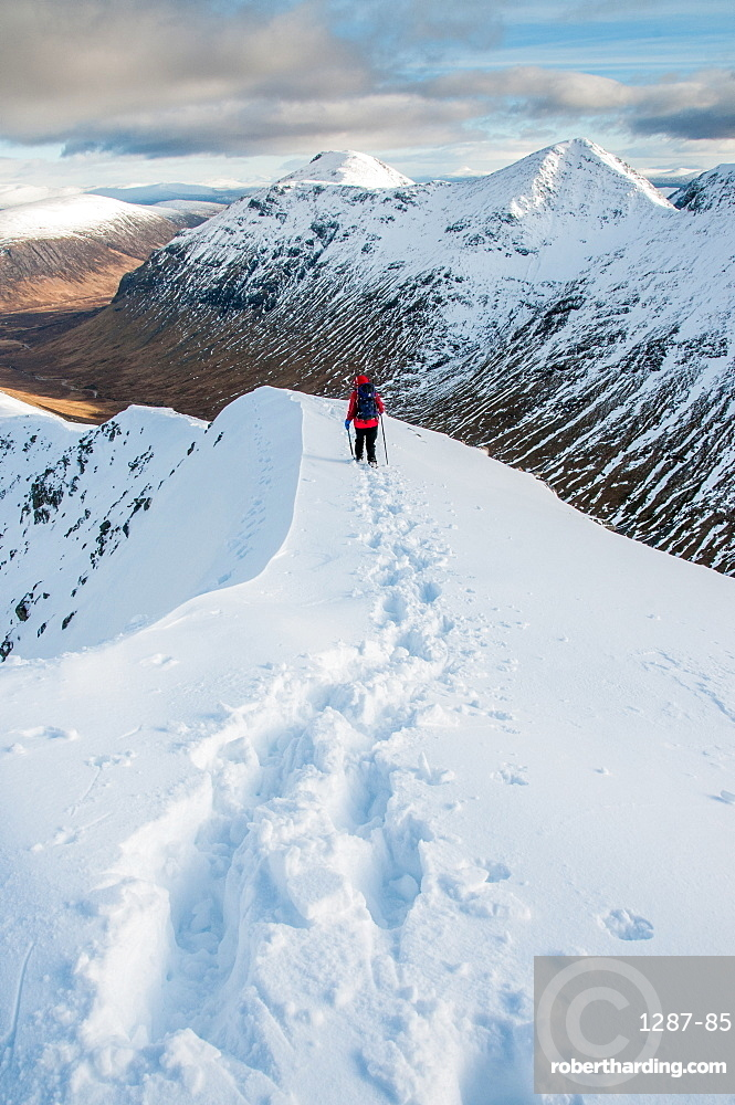 A female walker descending from the summit of Stob Dubh on Buchaille Etive Beag on a crisp winter day, Highlands, Scotland, United Kingdom, Europe
