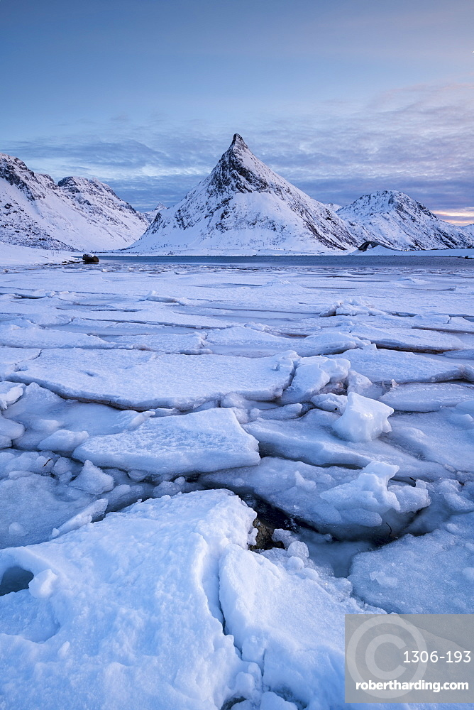 Snow covered steep mountain with ice formations in winter scene on Lofoten Islands, Arctic, Norway, Europe