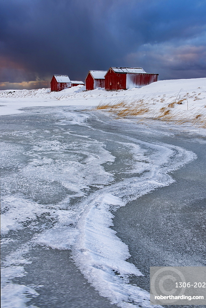 Typical fishermen houses Ice formations with dramatic sky in winter, Eggum, Lofoten Islands, Arctic, Norway, Europe