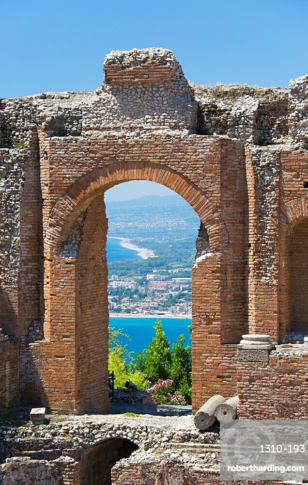 View from the Greek Theatre through arch to the Bay of Naxos, Taormina, Messina, Sicily, Italy