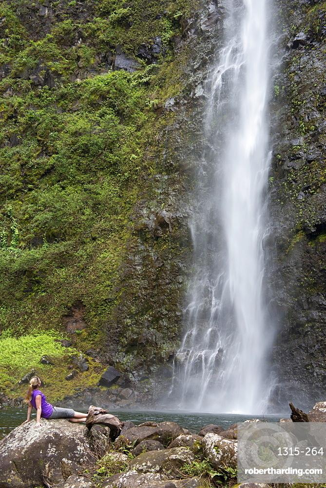 Hiker enjoying a waterfall along the famous Kalalau Trail, along Kauai's Na Pali Coast, Kauai, Hawaii, United States of America, North America