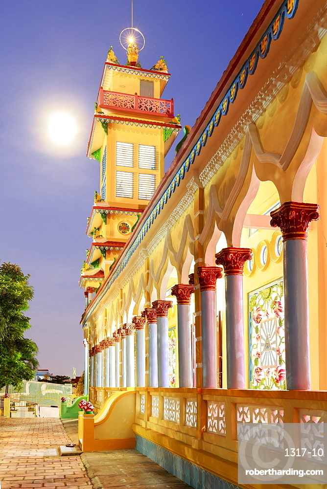 The Cao Dai temple in Vung Tau lit up at dusk with the full moon to the left of the tower