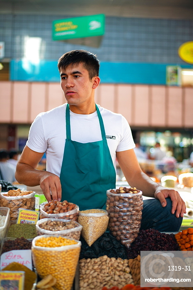A seller in Zelenyy Bazar also known as green bazar in Almaty. Farmer's market with stalls selling meat, vegetables & dry fruits