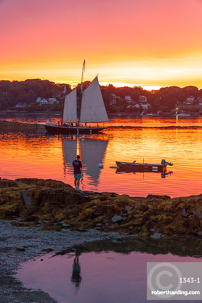 A schooner returns to dock at sunset at Bailey Island, Casco Bay, Maine, United States of America, North America