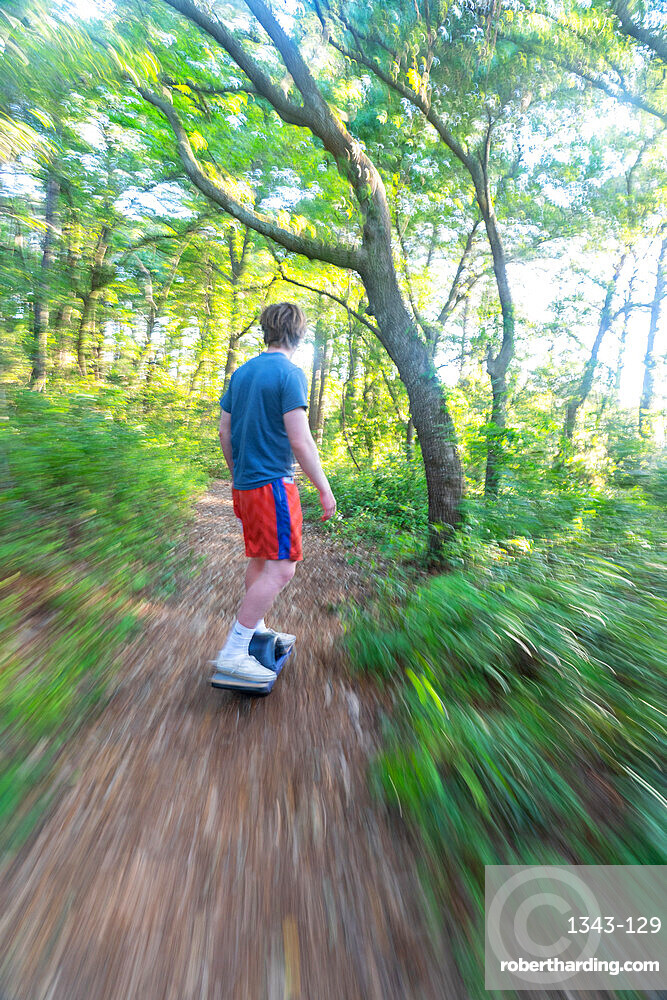 Christopher Brown rides his One-Wheel through a maritime forest near Nags Head, North Carolina, United States of America, North America