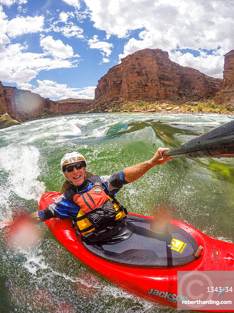 Skip Brown surfs his whitewater kayak on a glassy standing wave on the Colorado River through the Grand Canyon, Arizona, United States of America, North America