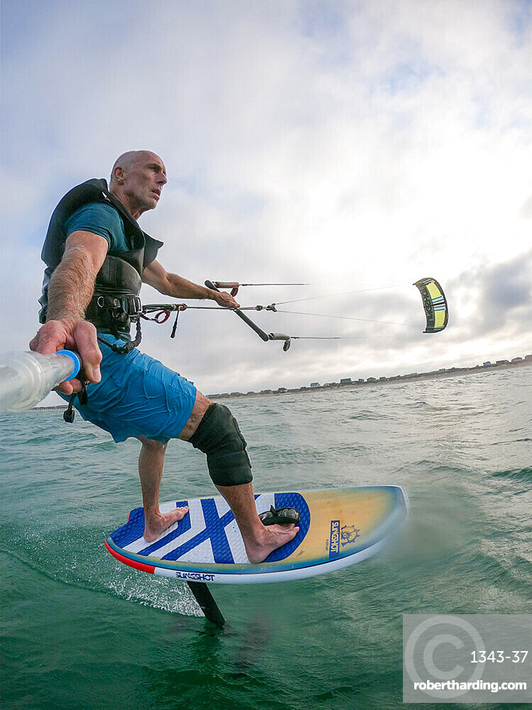 Photographer Skip Brown on his foiling kiteboard in the Atlantic Ocean off Nags Head, North Carolina, United States of America, North America