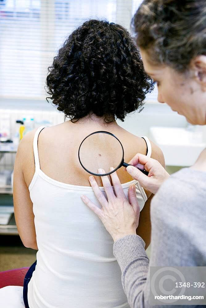 Dermatologist examining patient's moles.