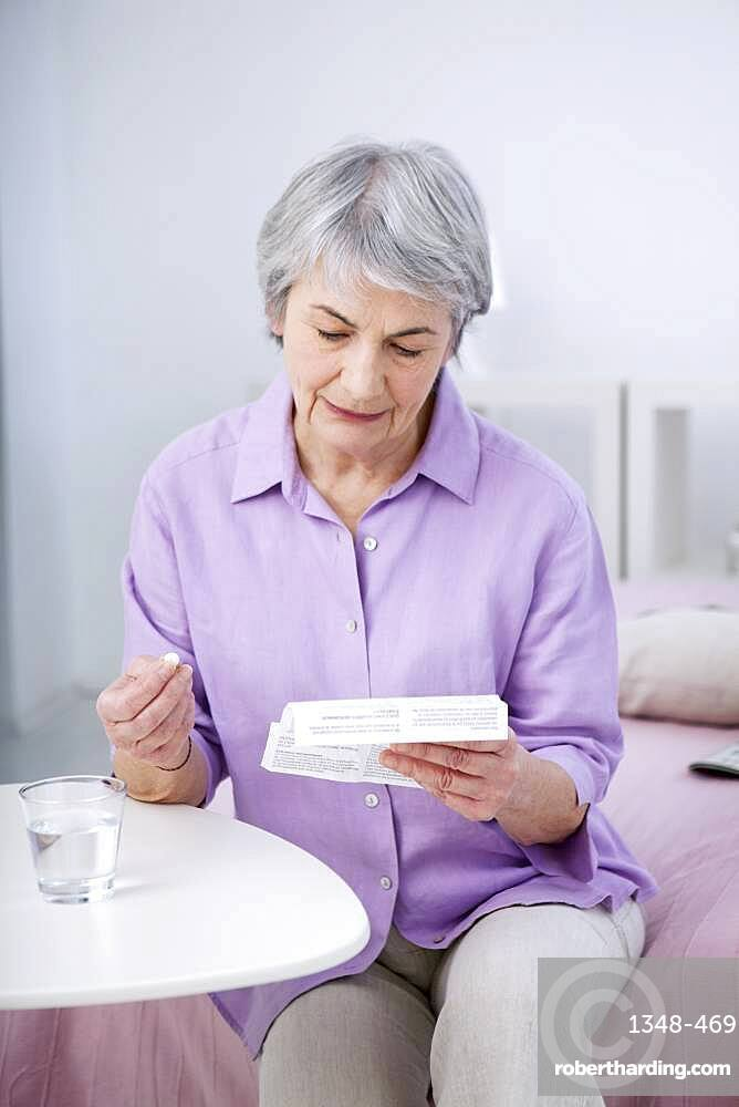Senior woman reading medication instruction sheet.