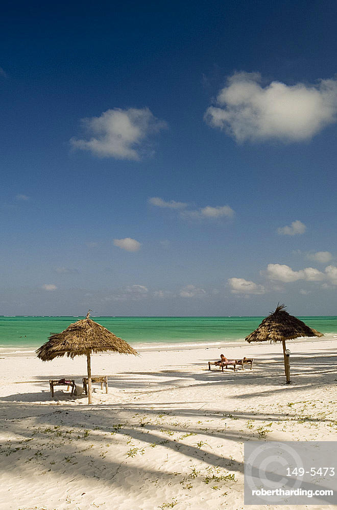 Thatched beach umbrellas and palm tree shadows on the beach at Paje, Zanzibar, Tanzania, East Africa, Africa