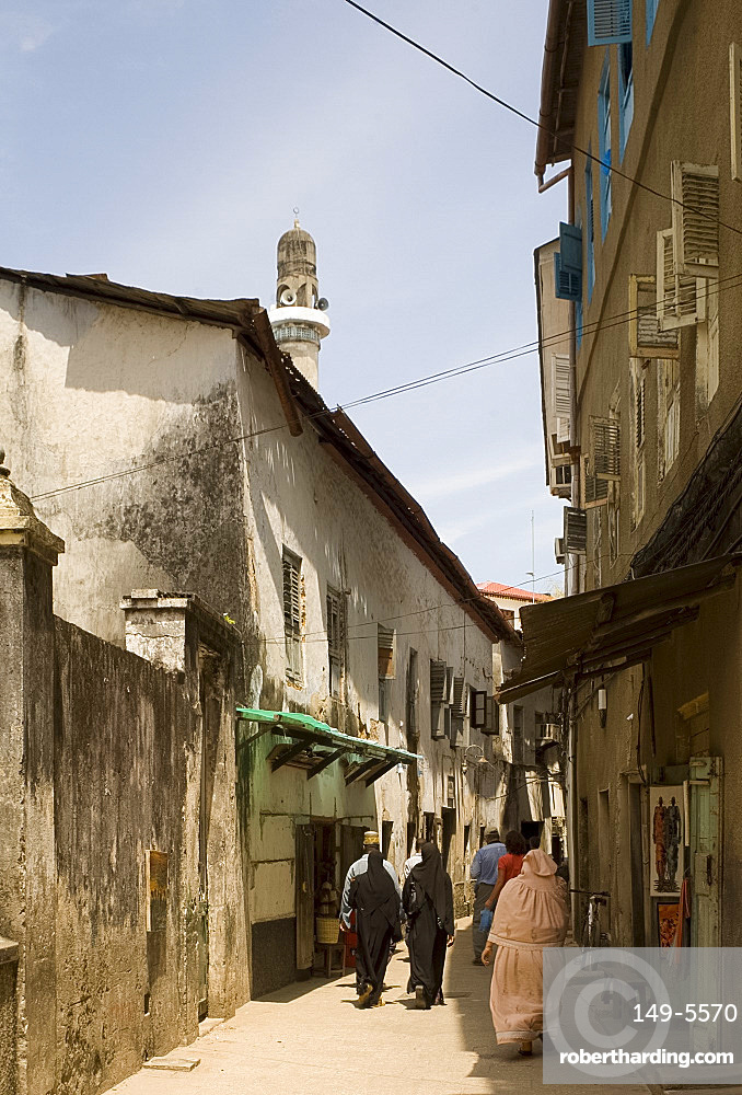 A busy street with a mosque minaret above in Stone Town, Zanzibar, Tanzania, East Africa, Africa