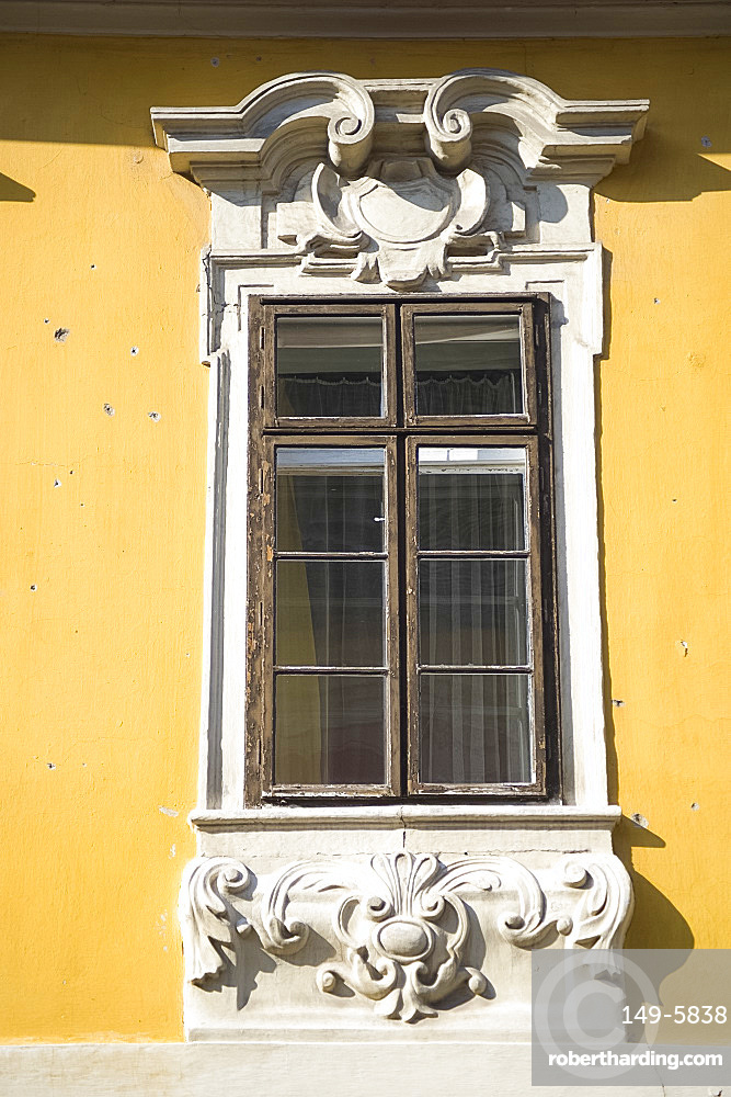 An old window surrounded by ornate carving in the Castle Hill section of Buda, Budapest, Hungary, Europe