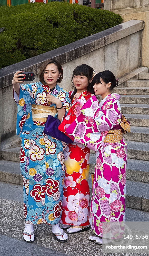 Young Japanese women dressed in colourful kimonos taking selfies in Kyoto, Japan, Asia