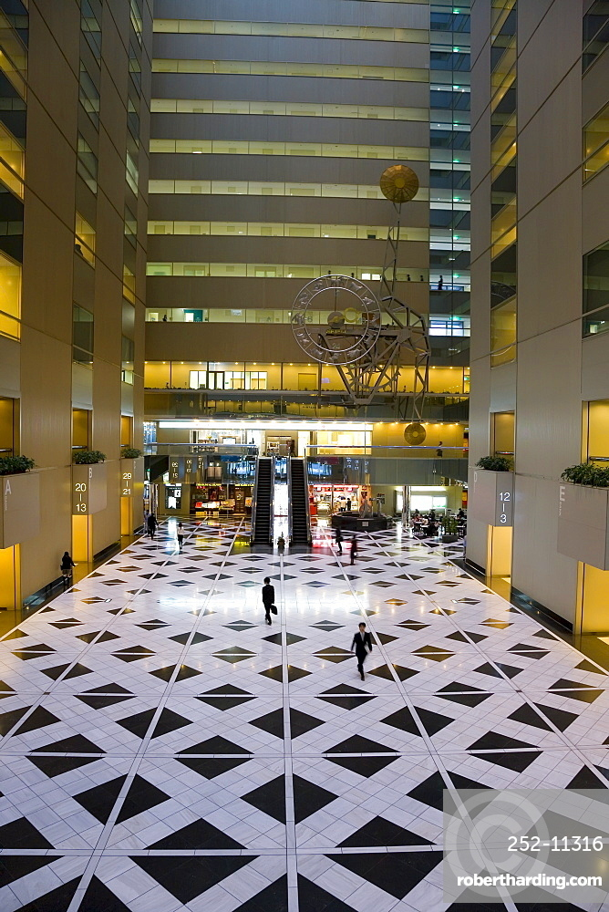 Elevated view of businessmen inside the Shinjuku NS Building, the interior is hollow with a 1600sq metre atrium illuminated through a glass roof, Shinjuku, Tokyo, Honshu, Japan, Asia