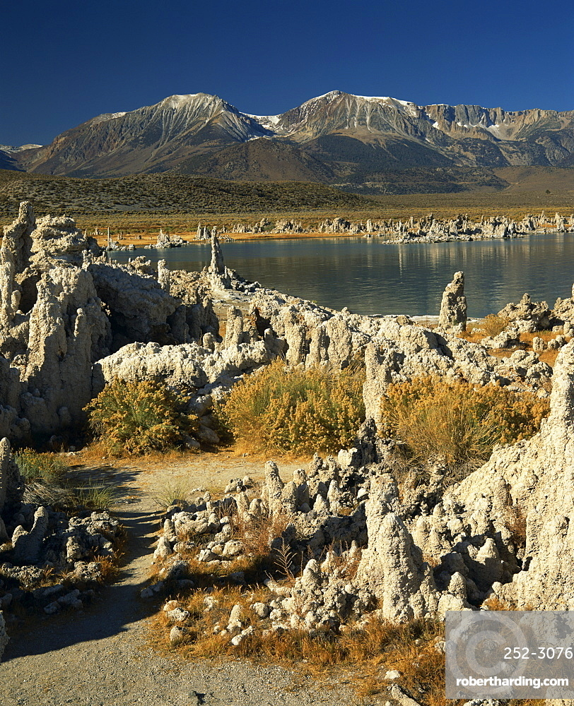 Tufas of calcium carbonate surround lake in Mono Lake Tufa State Reserve, with snow capped mountains in the background, in California, United States of America, North America