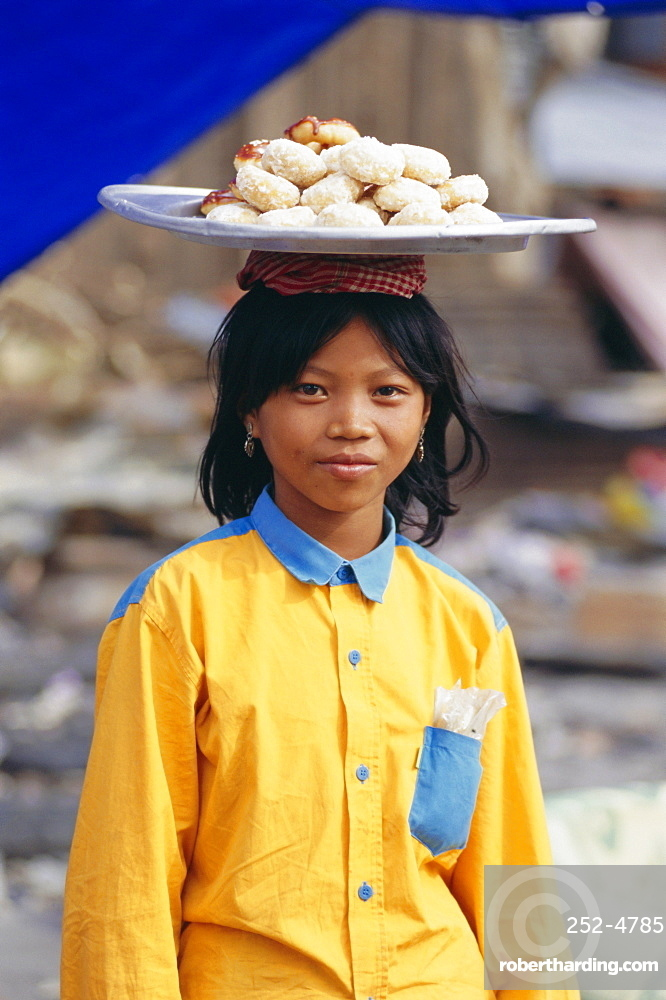 Portrait of a girl carrying buns, Phnom Penh, Cambodia, Indochina, Asia