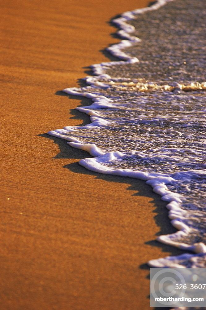 Close-up of surf on a sandy beach