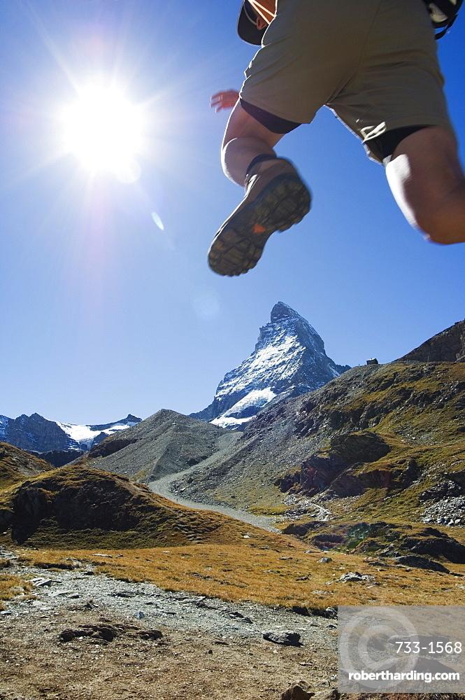 Hiker running on trail and the Matterhorn, 4477m,  Zermatt Alpine Resort, The Valais, Swiss Alps, Switzerland, Europe