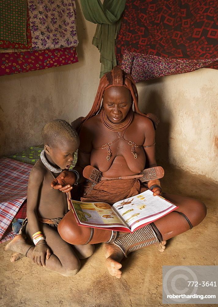 Himba woman and child reading, Kaokoland, Namibia, Africa