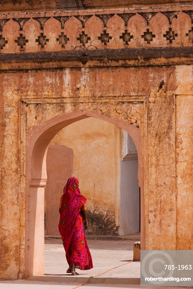 Lady in traditional dress walking through a gateway in the Amber Fort near Jaipur, Rajasthan, India, Asia
