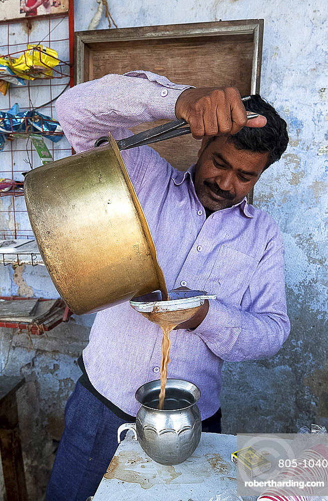 Chai wallah pouring chai from brass pan, using tongs, through sieve into tin vessel, in Diggi village market, Diggi, Rajasthan, India, Asia