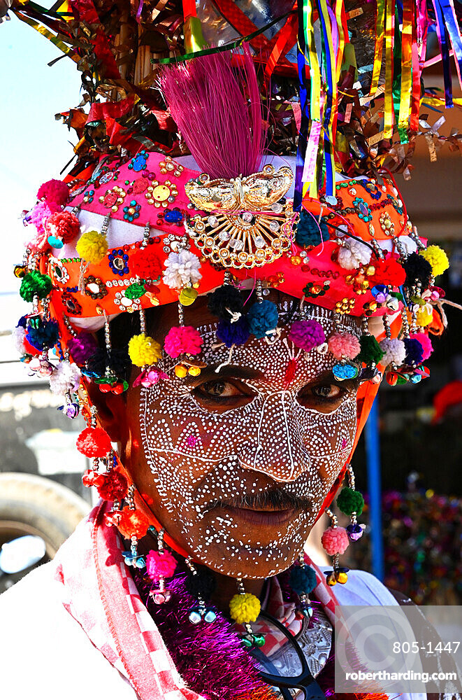 Adivasi tribal man, face decorated and wearing ornate decorated headgear to celebrate Holi festival, Kavant, Gujarat, India, Asia