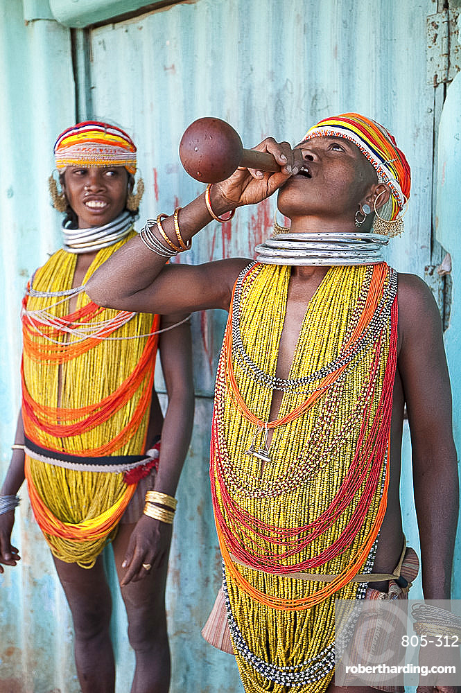 Two Bonda tribeswomen wearing traditional beads with beaded caps and metal necklaces drinking village alcohol from gourd vessel, Rayagader, Orissa, India, Asia