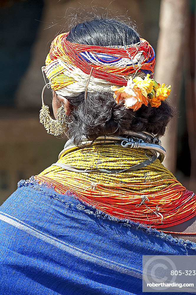 Bonda tribeswoman wearing blue cotton shawl over traditional bead costume, with beaded cap, large earrings and metal necklaces, Rayagader, Orissa, India, Asia