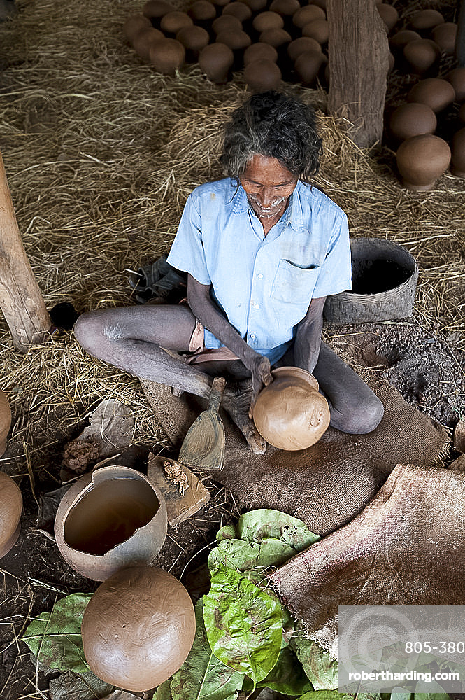 Potter making clay water pots in a thatched shelter in a rural village, near Rayagada, Orissa, India, Asia