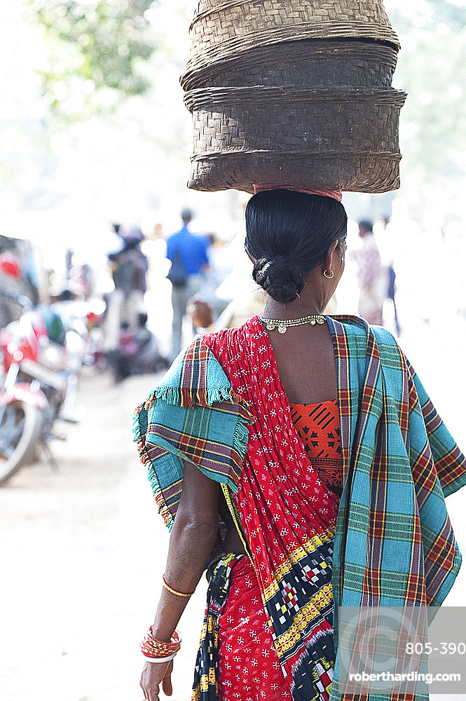 Woman at weekly tribal market wearing brightly coloured clothing and carrying baskets on her head, Bissam Cuttack, Orissa, India, Asia