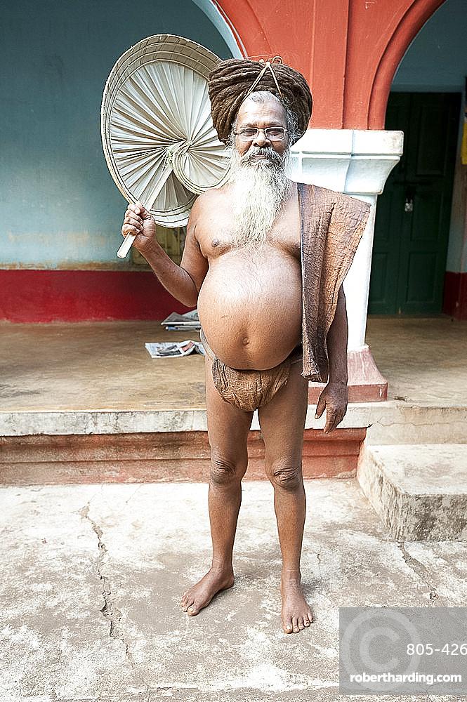 Joranda monk wearing tree bark loincloth, holding palm leaf fan, with uncut hair piled up on top of his head, Joranda, Orissa, India, Asia
