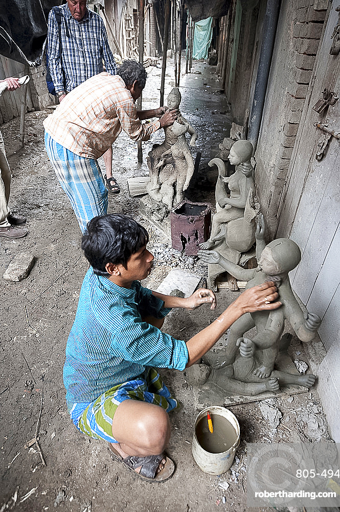 Master sculptors making models from clay from the River Hugli, to be painted for puja ceremonies, Kumartuli district, Kolkata, West Bengal, India, Asia