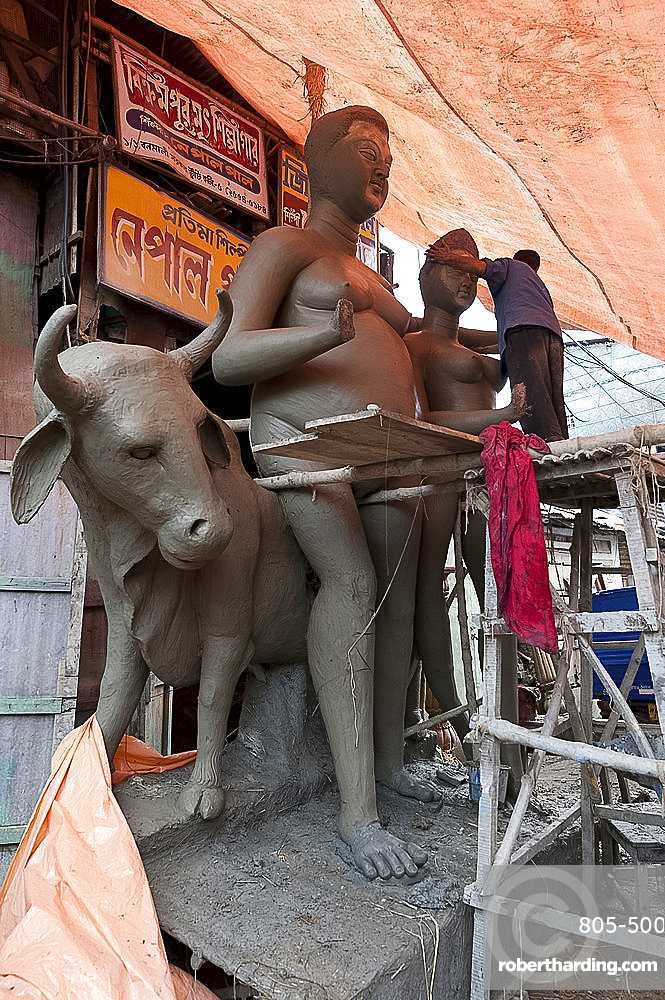 Sculptor working on large moulded deity and Nandi the bull, made from clay from the River Hugli, Kumartuli district, Kolkata, West Bengal, India, Asia
