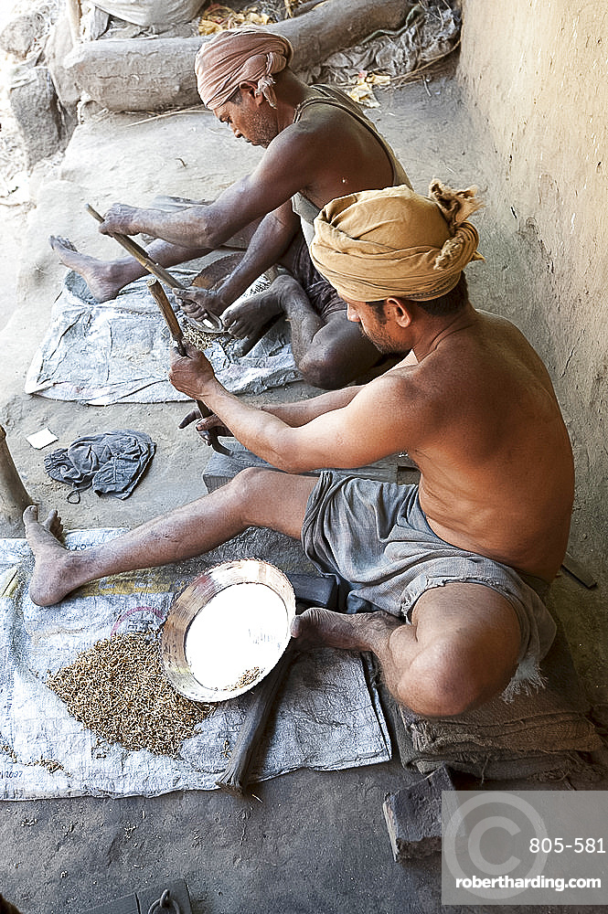 Two men smoothing surface of rough cast brass dishes outside village foundry, Hirapur, Orissa, India, Asia
