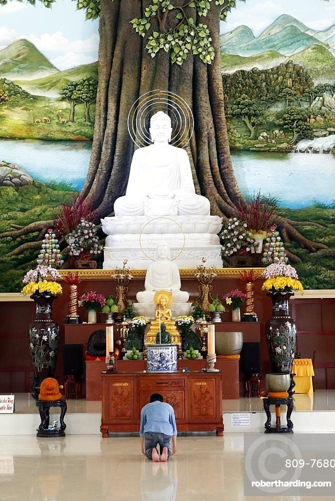 Van Linh Buddhist pagoda, man praying to the Buddha, the Enlightenment of the Buddha statue, An Hao, Vietnam, Indochina, Southeast Asia, Asia