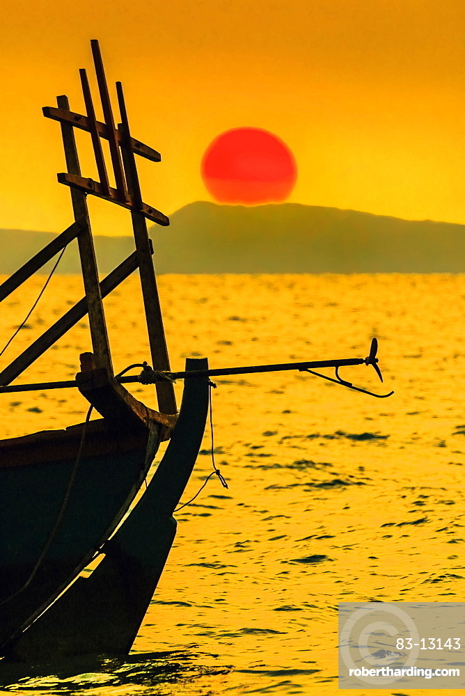 Big red setting sun beyond fishing boat moored off beach south of the city, Otres Beach, Sihanoukville, Cambodia, Indochina, Southeast Asia, Asia