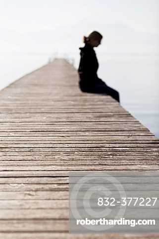 Woman sitting on a wooden jetty, Chiemsee Lake, Bavaria, Germany, Europe, PublicGround