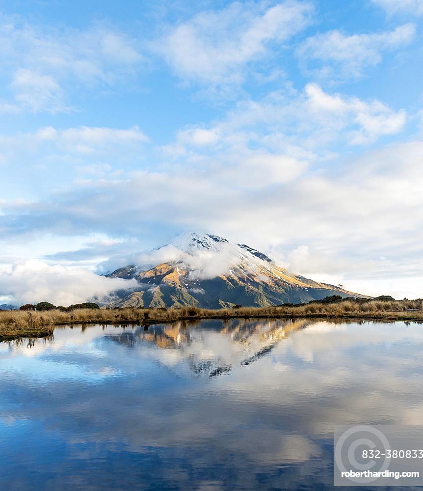Reflection in Pouakai Tarn, stratovolcano Mount Taranaki or Mount Egmont with cloud, Egmont National Park, Taranaki, New Zealand, Oceania