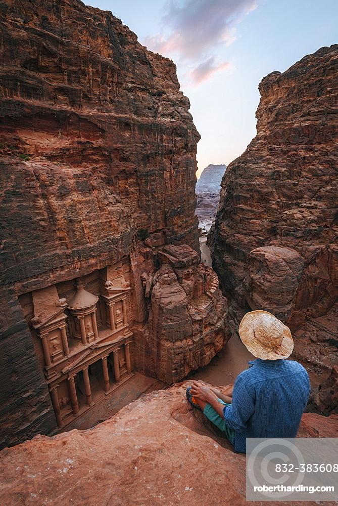 Tourist sits at the edge of a rock and looks from above into the canyon Siq, Pharaoh's treasure house beaten into the rock, facade of the treasure house Al-Khazneh, Khazne Faraun, Mausoleum, Nabataean city Petra, near Wadi Musa, Jordan, Asia