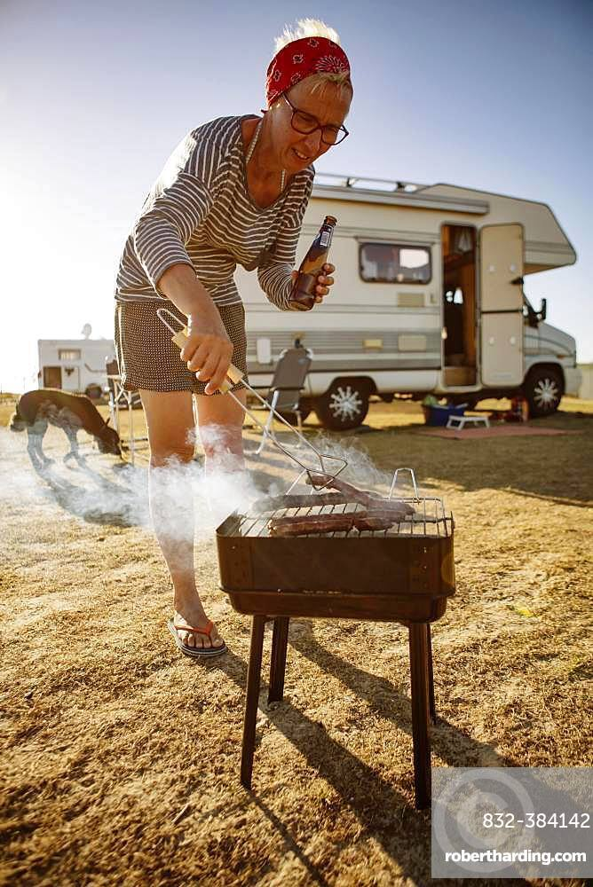 Woman camping, barbecuing in front of her motorhome, Portbail, Normandy, France, Europe