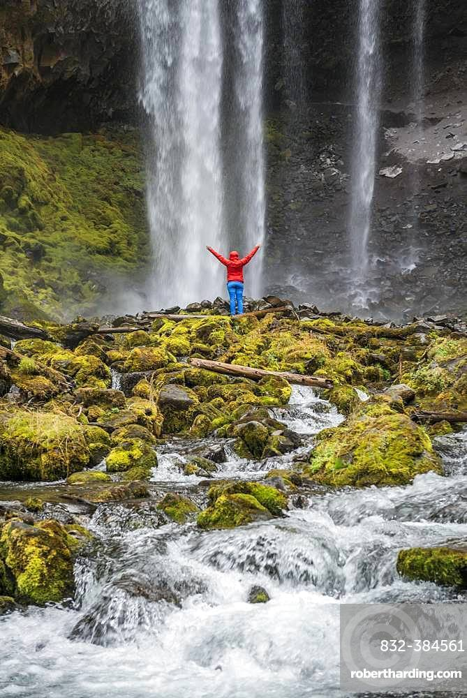 Hiker with raised arms in front of a high waterfall, water falls over a rocky outcrop, Tamanawas Falls, Wild River Cold Spring Creek, Oregon, USA, North America