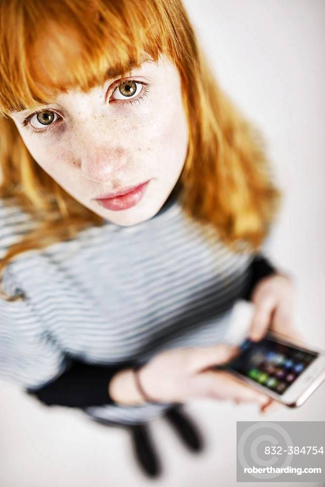 Girl, teenager, with smartphone in hand, looks thoughtfully into camera, studio shot, Germany, Europe